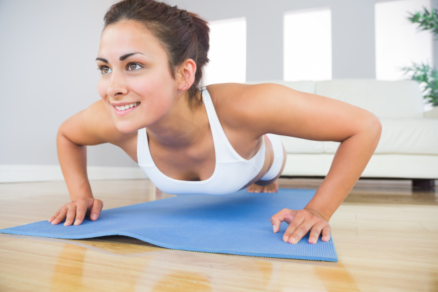 Young fit woman doing press ups on an exercise mat in her living